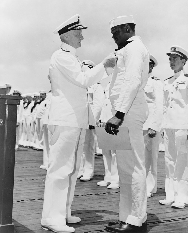 Nimitz rewards Miller with a Navy Cross for his actions on the Day of Infamy.