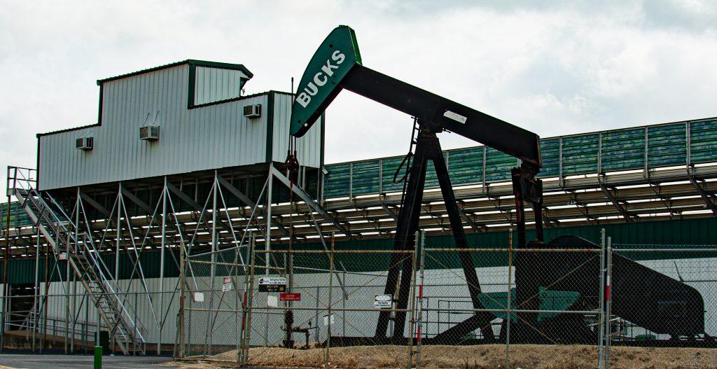 An oil derrick next to a football stadium pretty much describes a boomtown.